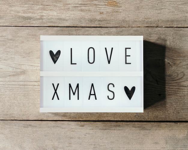 Liebe weihnachtstext in led-tafel mit holzhintergrund
