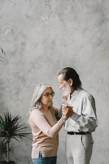 Liebe wird nie alt. fröhliches aktives altes romantisches paar im ruhestand, das im wohnzimmer tanzt.