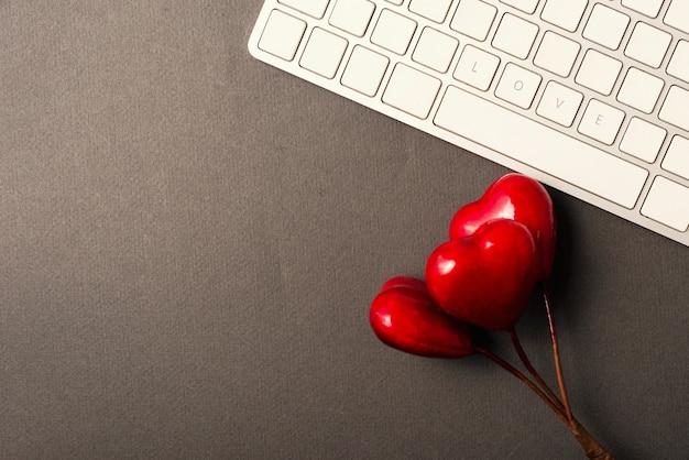 Liebe wort auf tastatur nahe roten herzen, valentinstagkonzept mit kopienraum