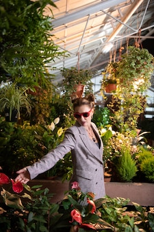 Liebe zu blumen. attraktive stilvolle geschäftsfrau, die ihre lieblingsblume betrachtet, während sie sie berühren möchte