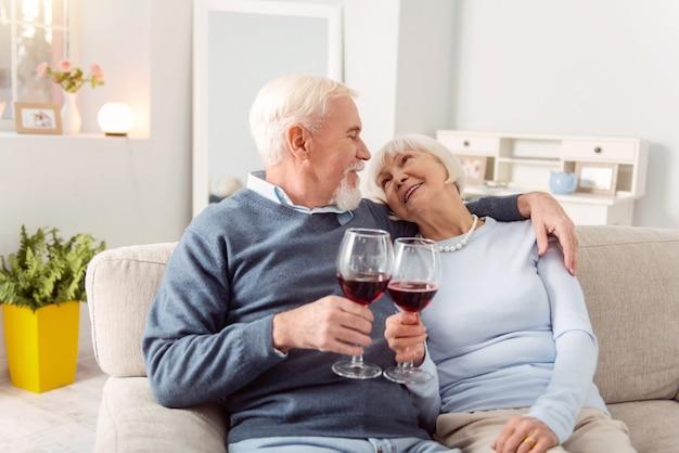 Lieben. angenehmes älteres ehepaar, das auf der couch kuschelt und einen toast zum lieben macht, mit der brille anstößt und sich liebevoll ansieht
