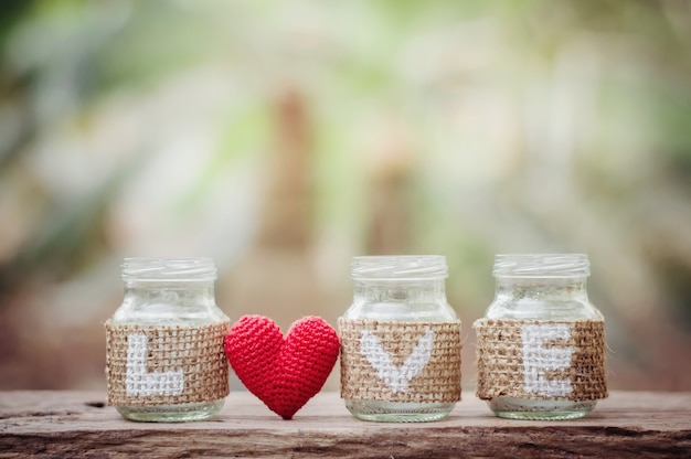 Lieben sie auf der flasche mit rotem herzen für valentinstag- oder hochzeitshintergrund