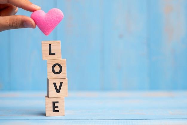 Lieben sie hölzerne würfel mit rosa herzformdekoration auf blauem tabellenhintergrund und kopieren sie raum für text. liebes-, romantik- und happy-valentine-ferienkonzept