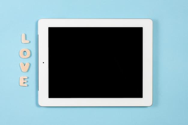 Lieben sie hölzernen text nahe der digitalen tablette mit schwarzer bildschirmanzeige auf blauem hintergrund