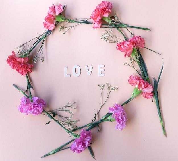 Lieben sie hölzernes wort mit geometrischem rahmen der frischen blumen auf blassem - rosa hintergrund