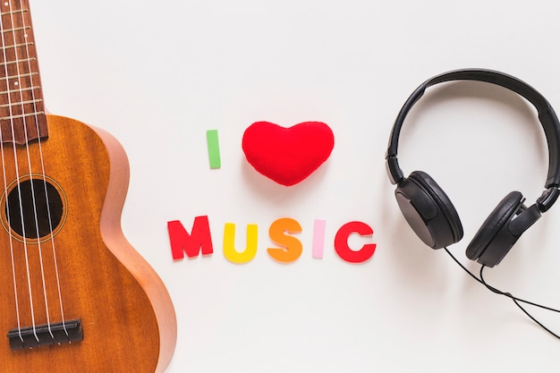 Lieben sie musiktext zwischen der musikalischen gitarre und dem kopfhörer auf weißem hintergrund