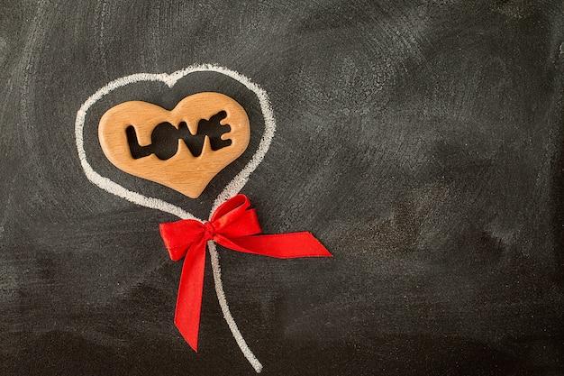 Lieben sie valentinsgrußherz und roten bogen auf der tafel