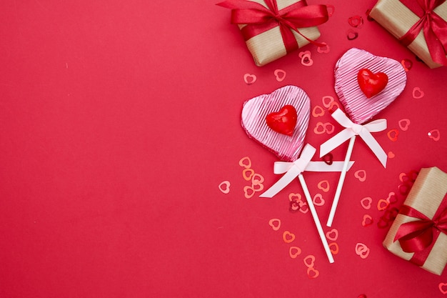 Lieben sie, valentinstagspott oben, wenn der lutscher in form eines herzens, eines geschenkboxex und eines funkelns auf rotem hintergrund lokalisiert ist, kopieren sie raum.