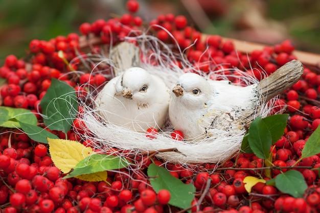 Lieben sie weiße vögel der keramik und ebereschenbeeren. vintage shabby chic stil. weiche, warme, zarte gefühle.
