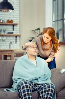 Liebende ehefrau. nette fürsorgliche frau, die hinter ihrem mann steht, während sie seine temperatur überprüft