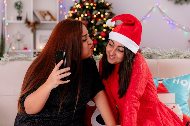 Liebende mutter hält telefon und gibt vor, ihre erfreute tochter mit weihnachtsmütze zu küssen, das telefon schaut, das auf couch sitzt, die weihnachtszeit zu hause genießt