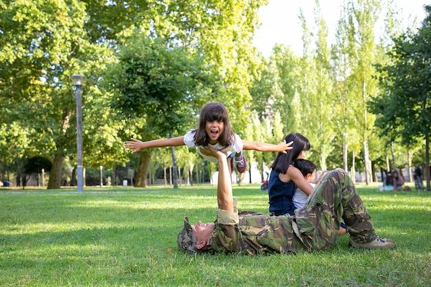 Liebender vater, der auf gras liegt und mädchen auf geraden händen hält. glücklicher vater in der militäruniform, die mit fröhlicher tochter spielt. mama und kleiner junge sitzen in ihrer nähe. familientreffen und wochenendkonzept