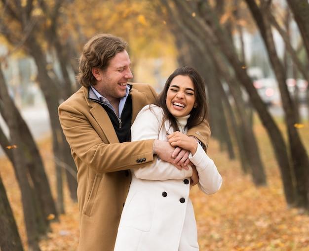 Liebendes kaukasisches paar, das im herbst im park spazieren geht