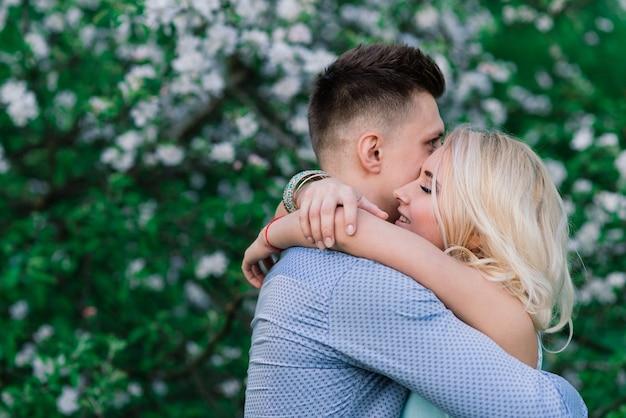 Liebendes paar, das auf der natur, sommerabend, sonnenuntergang küsst