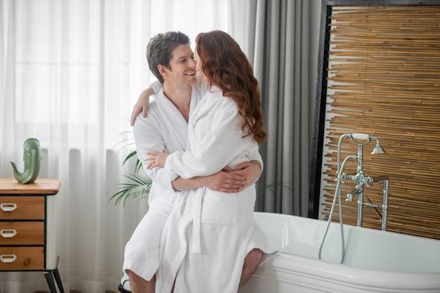 Liebendes paar. ein mann und eine frau in weißen bademänteln umarmen sich und fühlen sich liebevoll