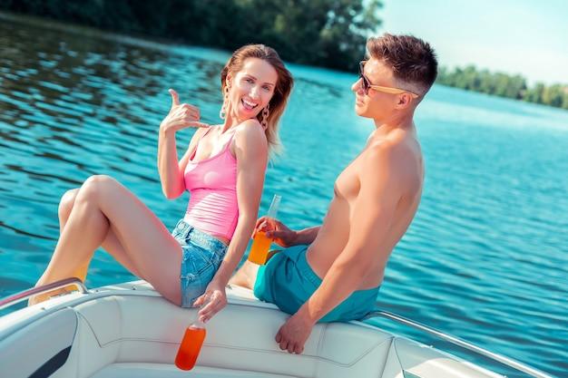 Liebendes paar. glückliche freundin, die die zeit ihres lebens neben ihrem freund hat, der im sommer in einem boot auf dem fluss sitzt