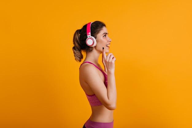 Liebenswerte brünette frau, die musik in kopfhörern hört