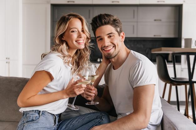 Liebenswerte frau, die champagner mit glücklichem lächeln trinkt. aufgeregte junge leute feiern jubiläum.