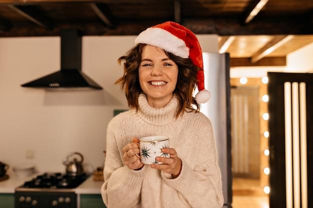 Liebenswerte hübsche frau mit lockigem haar, das gestrickte kleidung und weihnachtsmütze trägt, die auf der küche sitzt und auf weihnachtsfeier wartet