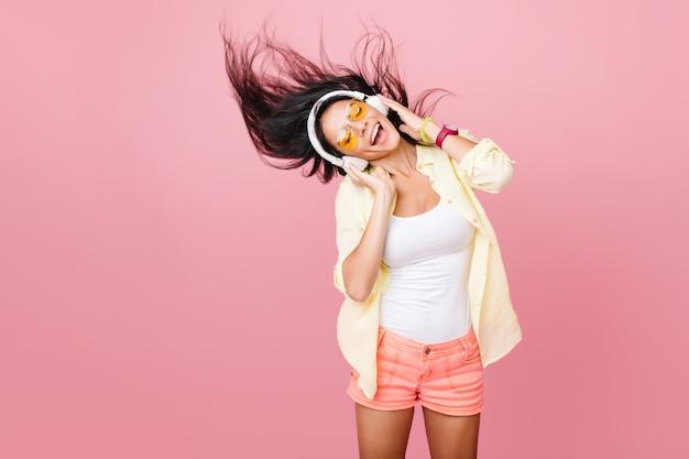 Liebenswerte lateinamerikanische frau im weißen trägershirt tanzt mit guter musik und wehendem haar. innenporträt des anmutigen aktiven asiatischen mädchens in den rosa shorts, die in den kopfhörern entspannen.