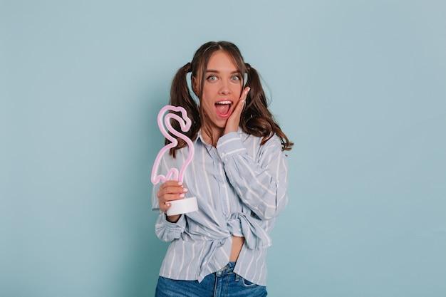 Liebenswertes charmantes mädchen, das blaues hemd hält, das rosa flamingo hält, ihren scheck berührt und über isolierte blaue wand lächelt