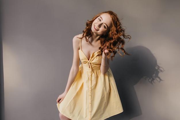 Liebenswertes ingwermädchen mit glücklichem lächeln tanzt auf grauer wand. entspannte kaukasische junge frau mit gewelltem haar, das im gelben kleid aufwirft.