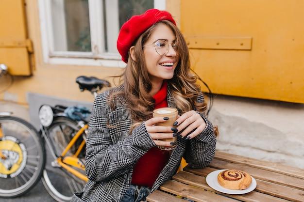 Liebenswertes mädchen mit schwarzer maniküre, die im straßencafé mit lächeln kühlt