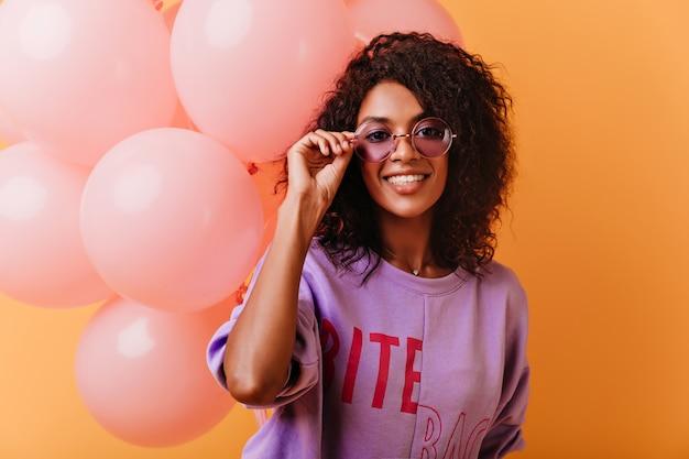 Liebenswertes weibliches modell in den gläsern und im lila hemd, die auf partei aufwerfen. enthusiastische schwarze junge frau, die spaß während des festes hat.