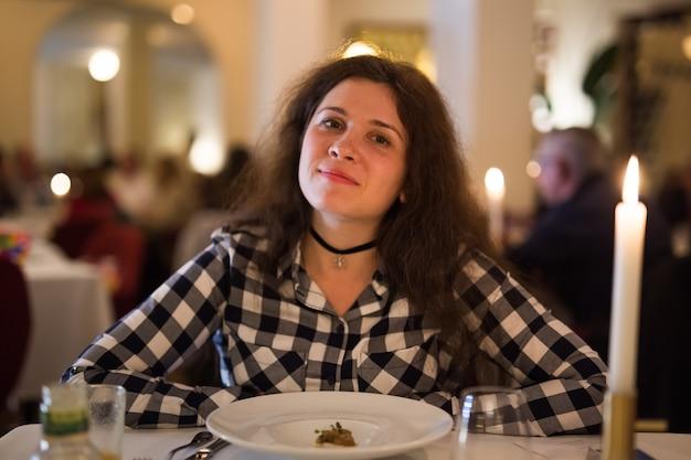 Liebes-, beziehungs- und datumskonzept - glückliche junge frau über kerzenlicht während des romantischen abendessens im restaurant.