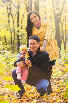 Liebes-, elternschafts-, familien-, jahreszeit- und personenkonzept - lächelndes paar mit baby im herbstpark