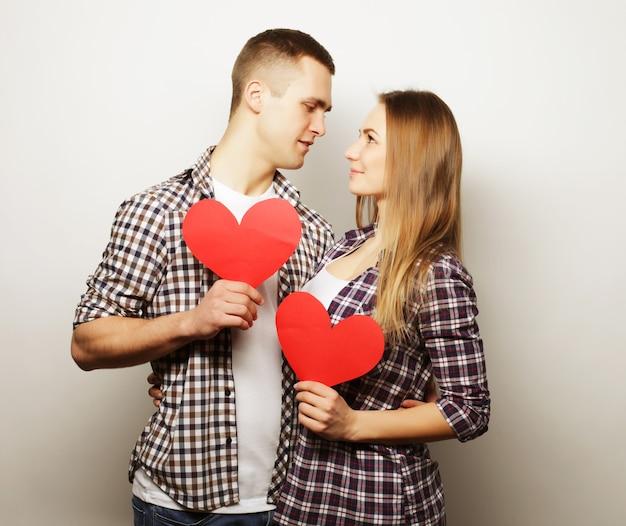 Liebes-, familien- und personenkonzept: glückliches paar in der liebe, die rotes herz hält.
