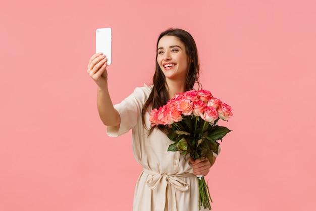 Liebes-, glücks- und feiertagskonzept. charmante schöne frau in hübschem kleid, hält blumen und lächelt am telefon, nimmt selfie mit schönen blumenstrauß, erhalten rosen als geschenk, rosa wand