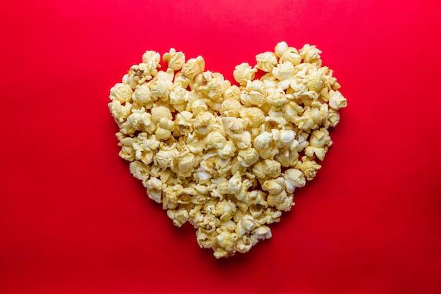 Liebes-kinokonzept des popcorns vereinbarte in einer herzform auf rotem hintergrund