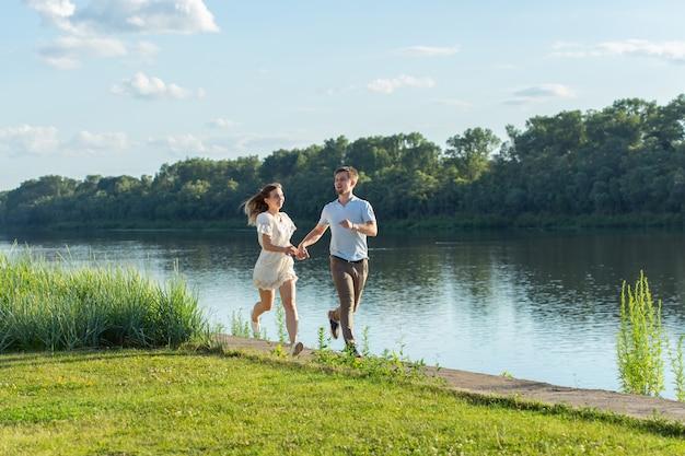 Liebes- und beziehungskonzept - der glückliche mann und die glückliche frau, die in einem park nahe einem see laufen.
