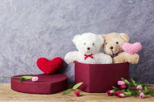 Liebes- und valentinsgrußtageskonzept des teddybären in der roten herzgeschenkbox auf hölzerner tabelle