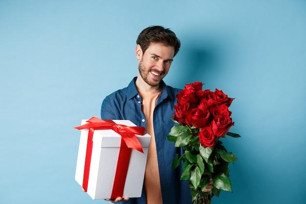 Liebes- und valentinstagkonzept. romantischer lächelnder mann, der ihnen geschenkbox und blumenstrauß am datum gibt, über blauem hintergrund stehend.