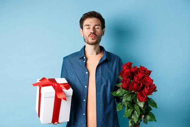 Liebes- und valentinstagkonzept. romantischer mann, der auf kuss wartet, geschenkbox und blumenstrauß der roten rosen für liebhaber am datum hält und über blauem hintergrund steht.