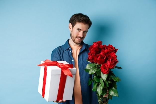 Liebes- und valentinstagkonzept. romantischer mann, der ihnen geschenkbox und blumenstrauß am datum gibt, über blauem hintergrund stehend.