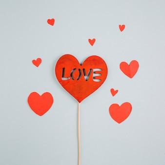 Liebesaufschrift auf papierherzen auf hölzernem stock