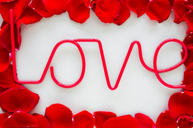 Liebesaufschrift mit den rosafarbenen blumenblättern auf grauer tabelle