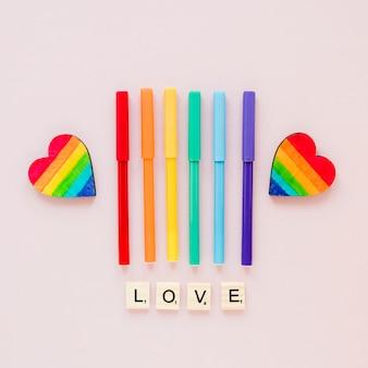 Liebesaufschrift mit regenbogenherzen und filzstiften