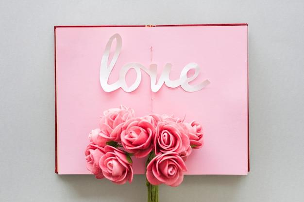 Liebesaufschrift mit rosenblumenstrauß auf notizbuch