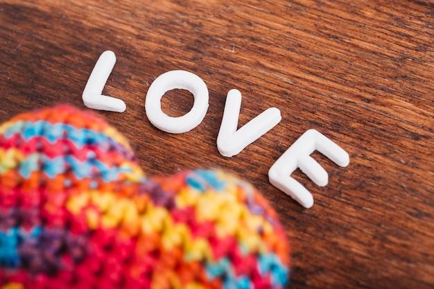 Liebesaufschrift mit weichem herzen auf holztisch