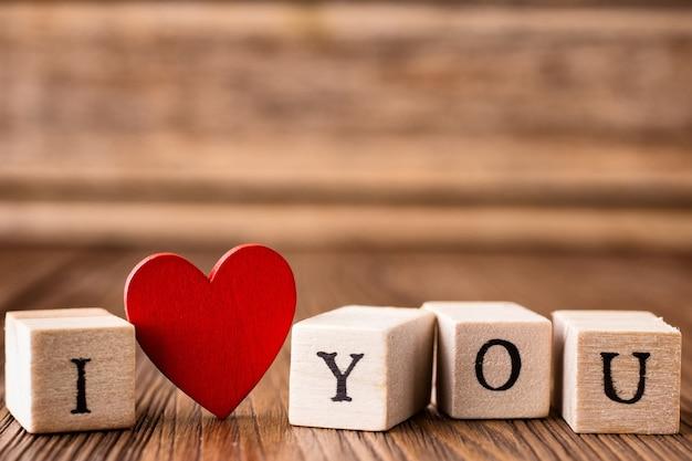 Liebesbotschaft in holzklötzen geschrieben. rotes herz.