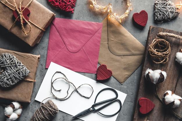 Liebesbotschaft valentinstag. vorbereitung, geschenkverpackung, baumwollblumen und postkarte