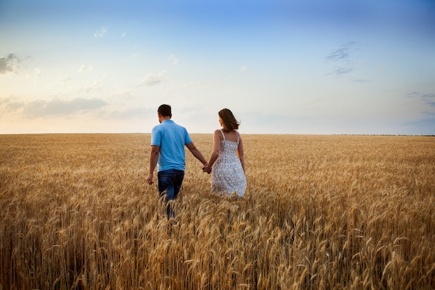 Liebesgeschichte. ein paar, eine frau und ein mann gehen ein weizenfeld entlang. der zukunft entgegen. leben außerhalb der stadt. natur. lebensstil