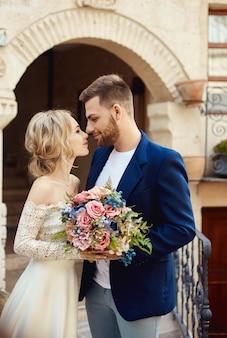 Liebesgeschichte einer frau und eines mannes. liebende paarumarmungen, ein schönes orientalisches paar. ein mann in einer jacke und eine frau in einem langen, luxuriösen, hellen kleid