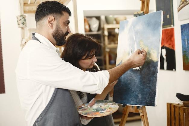 Liebesgeschichte eines erwachsenen paares in einem kunststudio. sie malen bilder, lachen, küssen sich. ihre gefühle, gefühle, liebe.