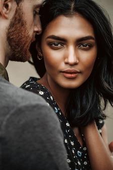 Liebesgeschichte in new york. mann küsst die junge indische frau, die sie zart und leidenschaftlich hält