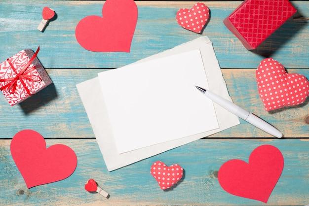 Liebesgrußkarte über hölzernem hintergrund auch im corel abgehobenen betrag. draufsicht mit kopienraum